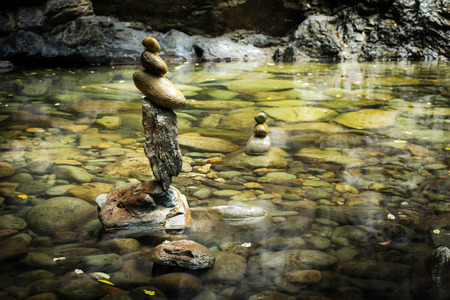 stack rock: Amazing tropical rain forest landscape with lake and balancing rocks tower for zen meditation practice. Nature background Stock Photo