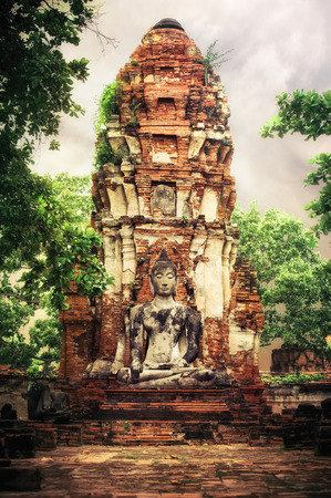 Asian religious architecture. Ancient sandstone sculpture of Buddha at Wat Mahathat ruins under sunset sky. Ayutthaya, Thailand travel landscape and destinations photo