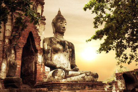Asian religious architecture. Ancient sandstone sculpture of Buddha at Wat Mahathat ruins under sunset sky. Ayutthaya, Thailand travel landscape and destinations Banco de Imagens