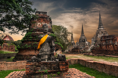 Asian religious architecture. Ancient sandstone sculpture of Buddha at Wat Phra Sri Sanphet  temple ruins under sunset sky. Ayutthaya, Thailand travel landscape and destinations photo