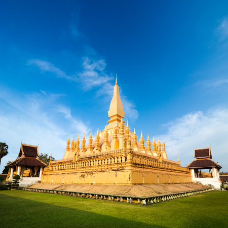 buddhist stupa: Religious architecture and landmarks. Golden buddhist pagoda of Phra That Luang Temple under blue sky. Vientiane, Laos travel landscape and destinations
