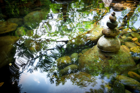 Amazing tropical rain forest landscape with lake and balancing rocks tower for zen meditation practice. Nature background 스톡 콘텐츠