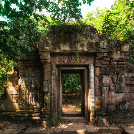 Ancient Khmer architecture. Entrance gate ruins of Baphuon temple with growing trees. Angkor Wat complex, Siem Reap, Cambodia travel destinations