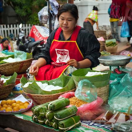 LUANG PRABANG, LAOS - DEC 8: Unidentified woman selling rice noodles at traditional asian food marketplace on Dec 8, 2013 in Luang Prabang, Laos