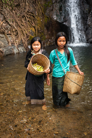 laos: VANG VIENG, LAOS - 15 DEC, 2013: Unidentified cute Asian girls with baskets washing vegetables in rain forest river near tropical waterfall