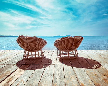 Amazing tropical beach landscape with chairs for relaxation on wooden terrace. Travel background in vintage style photo