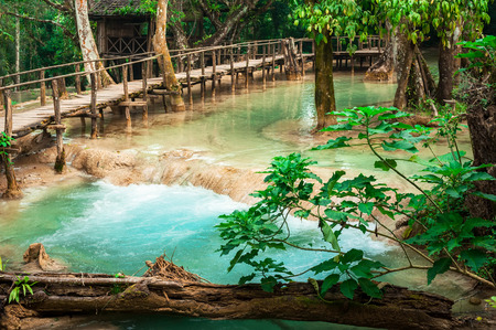 Jungle landscape of tropical rain forest landscape with wooden bridge and amazing turquoise water of Kuang Si cascade waterfall. Luang Prabang, Laos photo