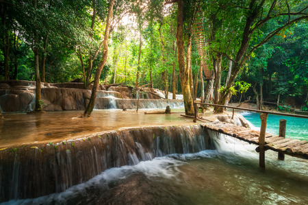 Jangle landscape of tropical rain forest landscape with wooden bridge and amazing turquoise water of Kuang Si cascade waterfall. Luang Prabang, Laos photo