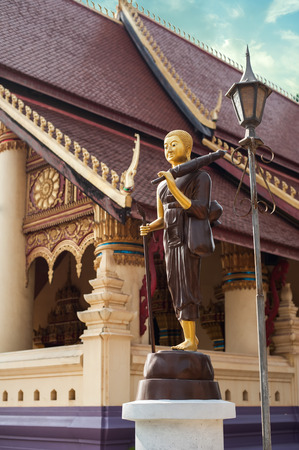 vientiane: Statue of walking Buddha in traditional theravada style with umbrella and bowl. Asian city religious architecture at public place. Vientiane, Laos