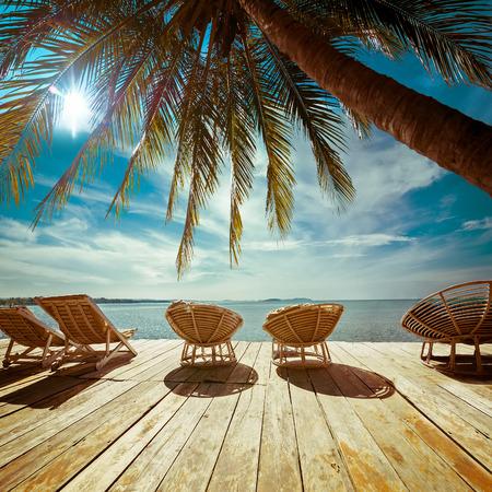 Verbazend tropisch strand landschap met palmbomen en stoelen voor ontspanning op een houten terras. Reizen achtergrond in vintage stijl