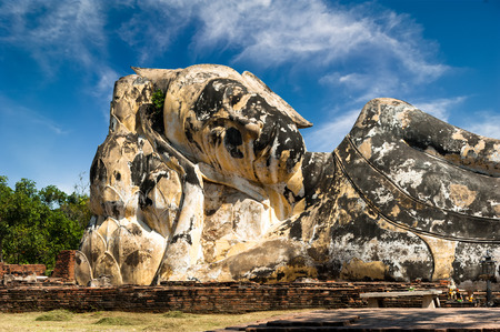 architecture ancient: Asian religious architecture. Ancient sandstone statue of reclining Buddha at Wat Lokayasutharam ruins. Ayutthaya, Thailand travel landscape and destinations
