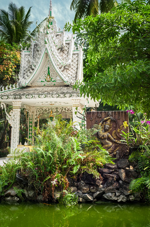 Buddhist carving and pagoda at outdoor park with decorative plants reflecting in pond. Asian city religious architecture at public place. Vientiane, Laos photo