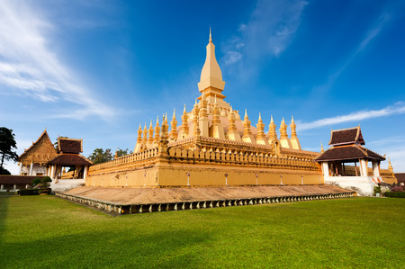 laos: Religious architecture and landmarks. Golden buddhist pagoda of Phra That Luang Temple under blue sky. Vientiane, Laos travel landscape and destinations