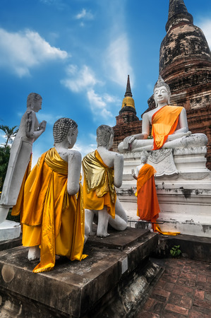 architecture ancient: Asian religious architecture. Ancient sandstone sculpture of praying Buddhas at Wat Yai Chai Mongkhon temple under blue sky. Ayutthaya, Thailand