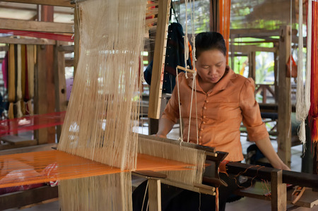 woll: LUANG PRABANG, LAOS - 8 DEC, 2013: Unidentified woman weaving silk in traditional way at manual loom. Laos