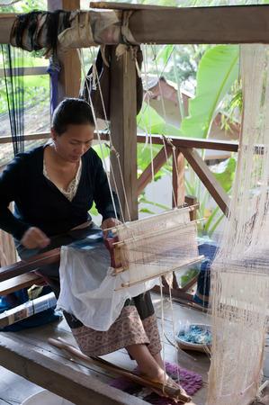 LUANG PRABANG, LAOS - 8 DEC, 2013: Unidentified woman weaving silk in traditional way at manual loom. Laos
