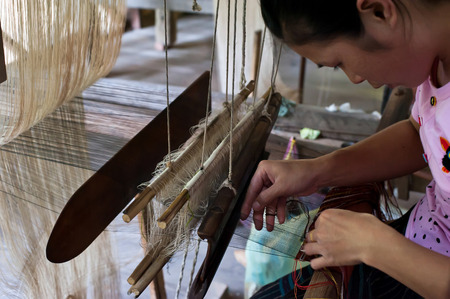 knotted: LUANG PRABANG, LAOS - 8 DEC, 2013: Unidentified woman weaving silk in traditional way at manual loom. Laos