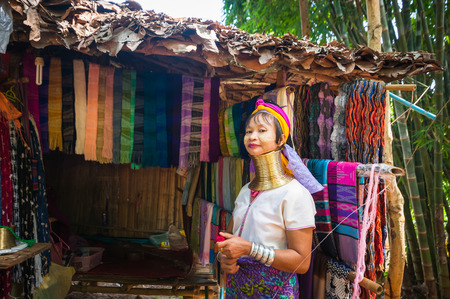 MAE HONG SON, THAILAND - DEC 4, 2013: Unidentified Karen (Kayan Lahwi Padaung) Long Neck woman with traditional brass coils selling hand made textile in tribe village. Chang Mai province, Thailand