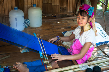 MAE HONG SON, THAILAND - DEC 4, 2013: Unidentified Karen (Kayan Lahwi Padaung) Long Neck woman with traditional brass coils working at hand loom in tribe village. Chang Mai province, Thailand