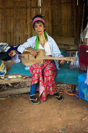 MAE HONG SON, THAILAND - DEC 4, 2013: Unidentified Karen (Kayan Lahwi Padaung) Long Neck woman with traditional brass coils and clothes sings folk song in tribe village. Chang Mai province, Thailand
