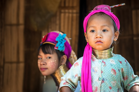 MAE HONG SON, THAILAND - DEC 4, 2013: Unidentified Karen (Kayan Lahwi Padaung) Long Neck girl and young woman with traditional brass coils and clothes in tribe village. Chang Mai province, Thailand