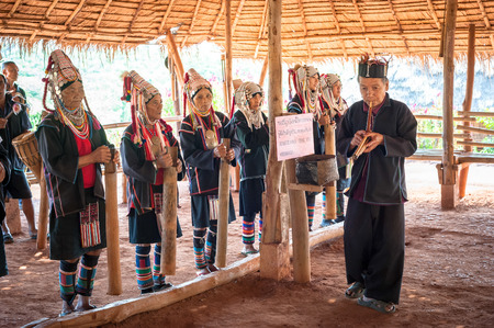 CHIANG RAI, THAILAND - DEC 4, 2013: Unidentified Akha tribe people in traditional  clothes and jewelry performing folk dance and songs in village. Thailand