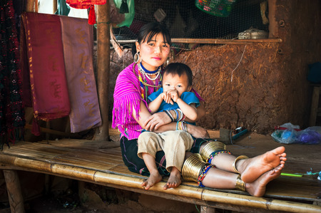MAE HONG SON, THAILAND - DEC 4, 2013: Unidentified Karen (Kayan Lahwi Padaung) Long Neck woman wearing traditional brass coils and clothes with her son in tribe village. Chang Rai province, Thailand