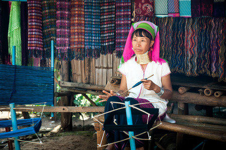 long neck: MAE HONG SON, THAILAND - DEC 4, 2013: Unidentified Karen (Kayan Lahwi Padaung) Long Neck woman with traditional brass coils working at hand loom in tribe village. Chang Mai province, Thailand
