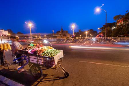 penh: Vendor selling fruits at evening asian city. Scene of night life at most popular tourist street near Royal Palace in capital city Phnom Penh, Cambodia Stock Photo
