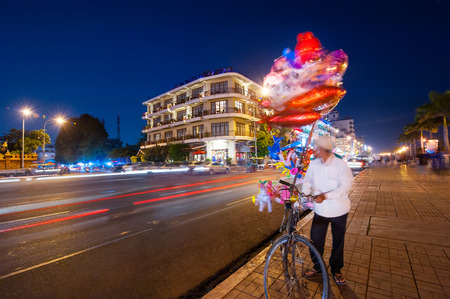penh: Vendor on bicycle selling bright balloons at evening asian city. Scene of night life at most popular tourist street near Royal Palace in capital city Phnom Penh, Cambodia