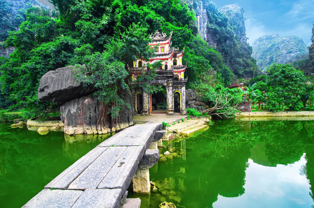 travel: 호수와 돌 다리와 야외 공원 풍경. 고대 비히 동 탑 복잡한 게이트 입구. 닌빈, 베트남 여행 목적지