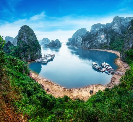 ハロン湾、南シナ海、ベトナム、東南アジアでの石灰岩の岩の間で浮かぶ観光ジャンク