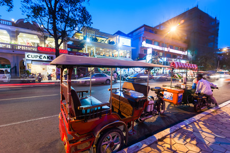 penh: PHNOM PENH, CAMBODIA - DEC 29, 2013: Moto taxi at asian city. Scene of night life at most popular tourist street near Mekong river in capital city Phnom Penh, Cambodia Editorial