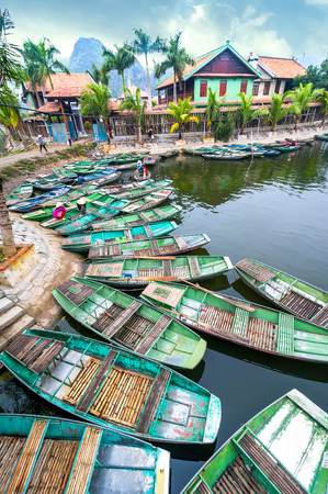 freshwater sailor: Vietnamese woman with conical hat Amazing morning view with Vietnamese boats at river. Tam Coc, Ninh Binh,. Vietnam travel landscape and destinations Stock Photo