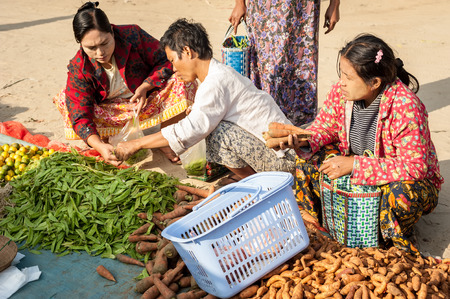 BAGAN, MYANMAR - JANUARY 16, 2014: Burmese people shopping spices, greengrocery and local goods at traditional asian marketplace. Burma travel destinations