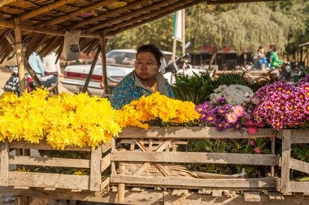 BAGAN, MYANMAR - JANUARY 16, 2014: Burmese woman selling flowers at traditional asian marketplace. Burma travel destinations