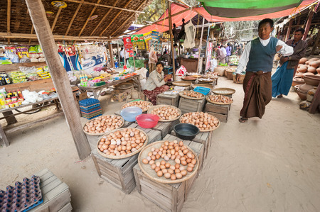 hen and chicken: BAGAN, MYANMAR - JANUARY 16, 2014: Burmese people selling eggs and local goods at traditional asian marketplace. Burma travel destinations