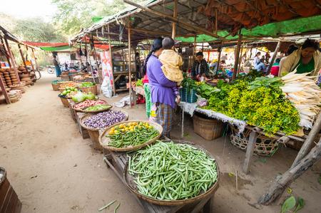 BAGAN, MYANMAR - JANUARY 16, 2014: Burmese women selling greengrocery and traditional local goods at asian marketplace. Burma travel destinations