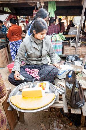 BAGAN, MYANMAR - JANUARY 16, 2014: Burmese woman selling handmade tofu cheese at traditional asian marketplace. Burma travel destinations
