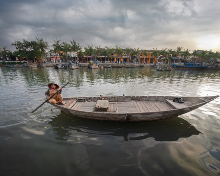 floating market: HOI AN, VIETNAM - FEBRUARY 3, 2014: Vietnamese women sitting in a traditional boat on the river under sunset sky. Hoi An, Vietnam famous ravel landscape and destinations