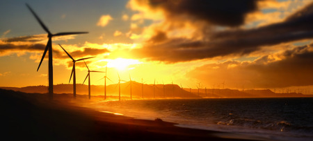 Wind turbine power generators silhouettes at ocean coastline at sunset. Alternative renewable energy production in Philippines. Two images panorama, tilt shift effect