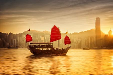 Zonsondergang skyline van Hong Kong met traditionele cruise zeilboot bij de haven van Victoria