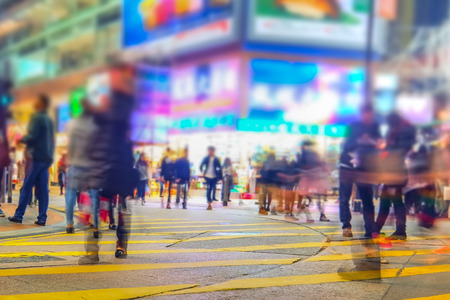 Blurred image of people moving in crowded night city street with sopping malls. Hong Kong. Blur effect