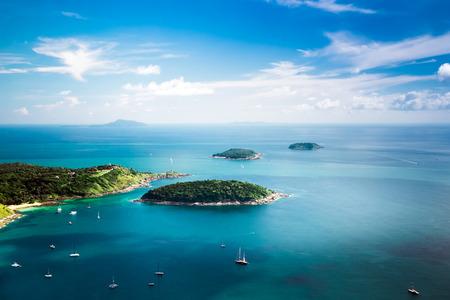 Tropical ocean landscape with Koh Kaeo island at turquoise ocean waives with boats near Ya Nui beach. Rawai, Phuket, Thailand