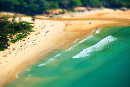 Tropical sandy beach landscape from high view point tilt shift effect. Beautiful turquoise ocean and people relaxing in waives. Rawai, Ya Nui beach, Phuket, Thailand photo