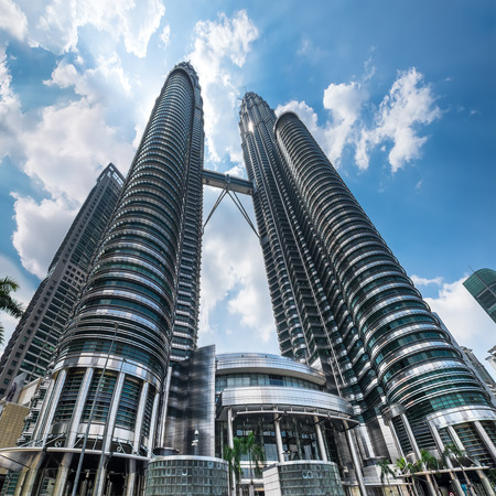 KUALA LUMPUR, MALAYSIA - March 4, 2015: Cloudscape view of the Petronas Twin Towers at KLCC City Center. The most popular tourist destination in Malaysian capital Фото со стока - 38141263