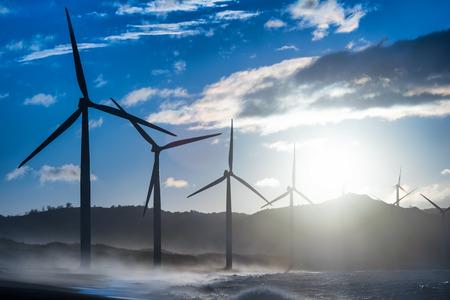 Wind turbine power generators silhouettes at evening ocean coastline. Alternative renewable energy production in Philippines photo