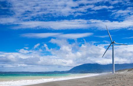 Wind turbine power generators silhouettes at ocean coastline. Alternative renewable energy production in Philippines photo