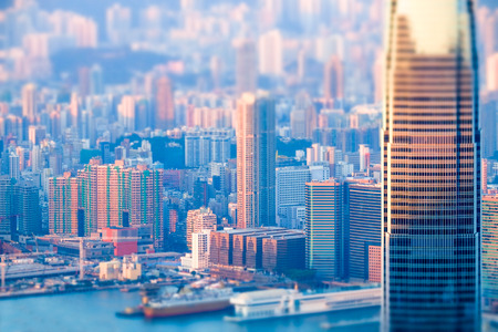 Abstract futuristic cityscape with modern skyscrapers. Hong Kong aerial view evening panorama. Tilt shift effect