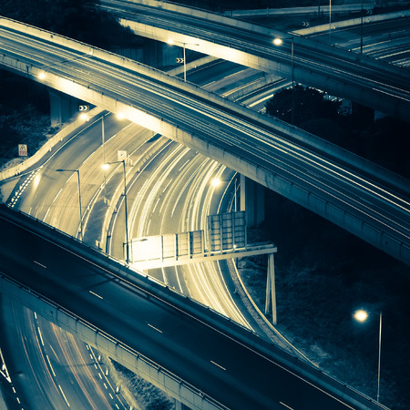 Abstract night view of highway interchange with moving cars. Hong Kong city aerial background in vintage style Фото со стока